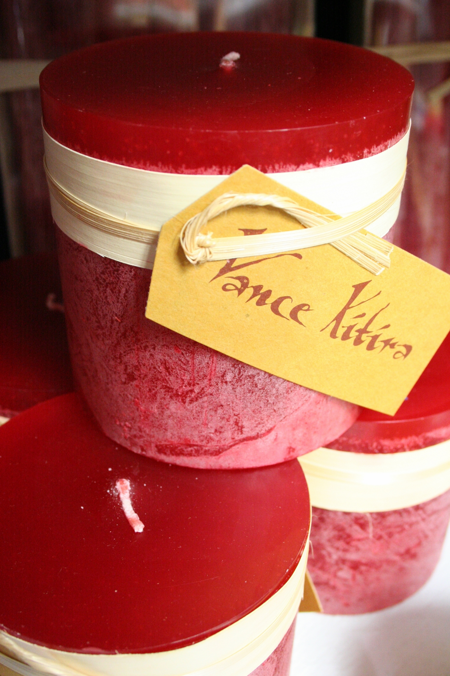 Red Vance Kitira candles on white shelf with brown label