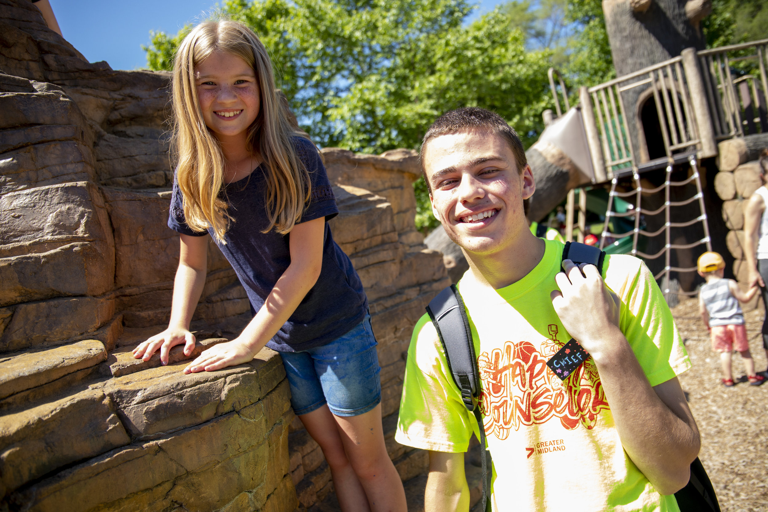 Griffin, once a camper that climbed this rock, now hangs with Lexi as she plays with friends.