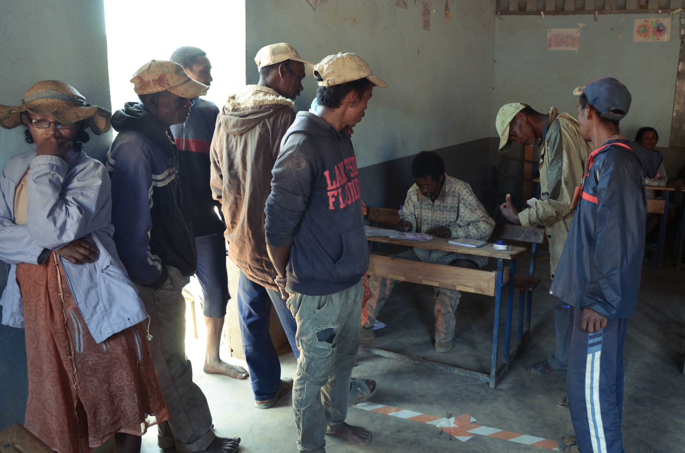 Village members line up to cast votes. Photo: Alizé Carrère