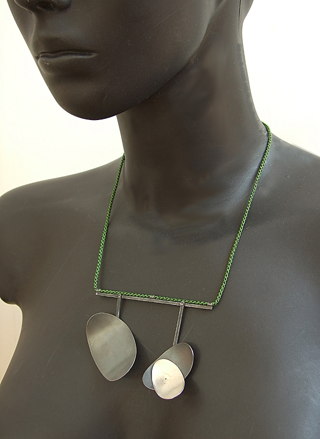 Model wearing green & black Kumihimo silk braided necklace with two large, textured, partially oxidised, domed oval silver pendants. HBM087.
