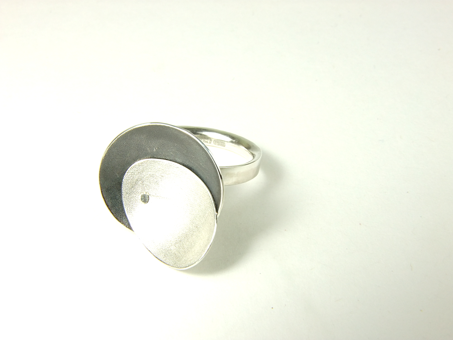 Side view of Argentium silver ring with two textured and domed oval top pieces, riveted together & partially oxidised. HBM084A