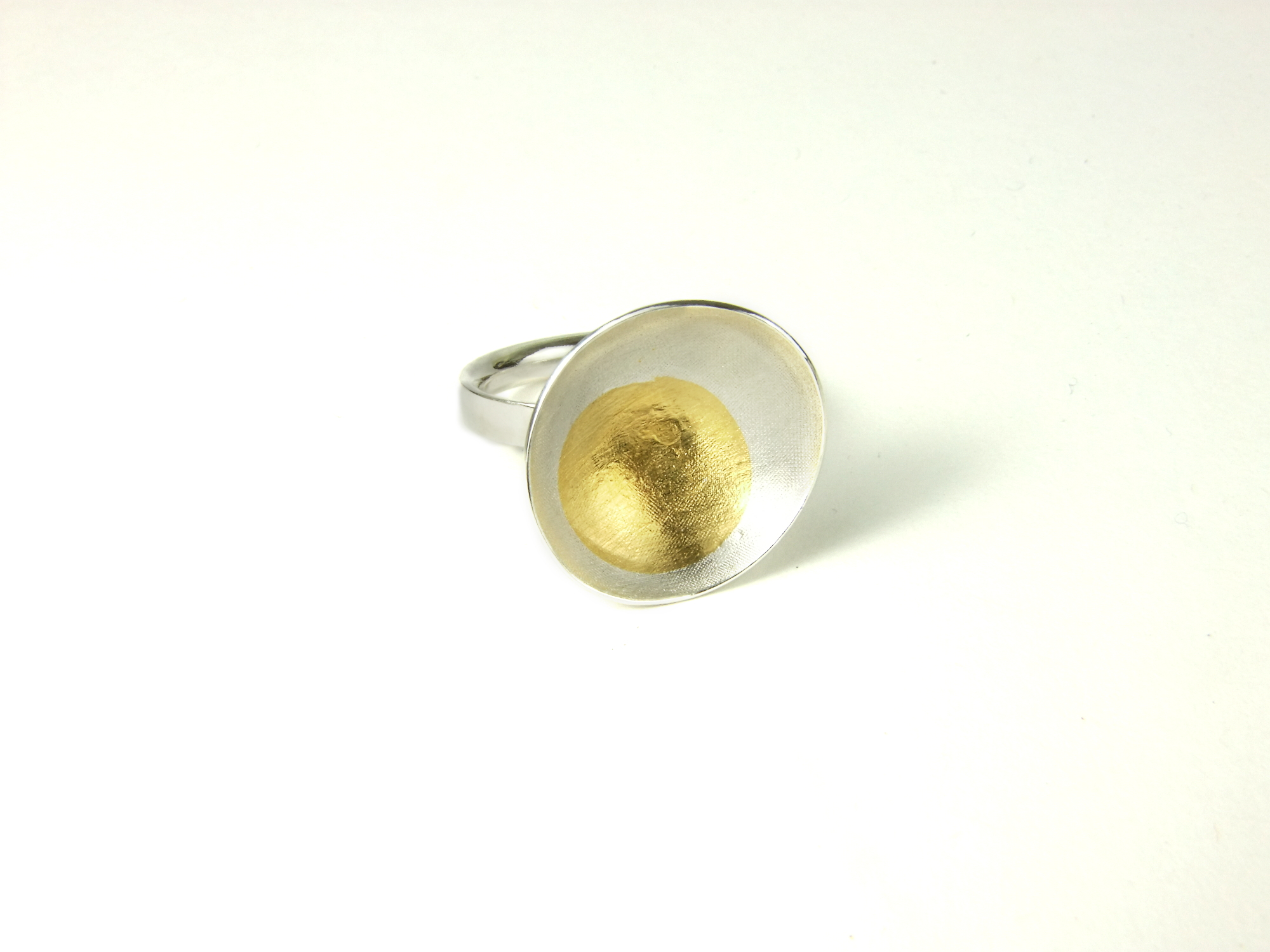Front view of Argentium silver ring with large domed and textured oval with a round Keum-Boo detail in 22 ct yellow gold. (HBM089A)