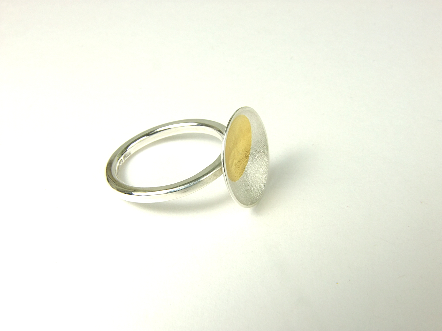 Side view of Argentium silver ring with shallow textured oval with a round Keum-Boo detail in 22 ct yellow gold. (HBM089B)