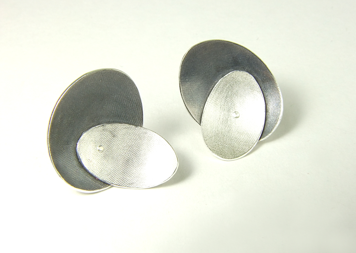 Front view of small Argentium silver ear studs with two domed oval shapes, partially oxidised. (HBM088B)
