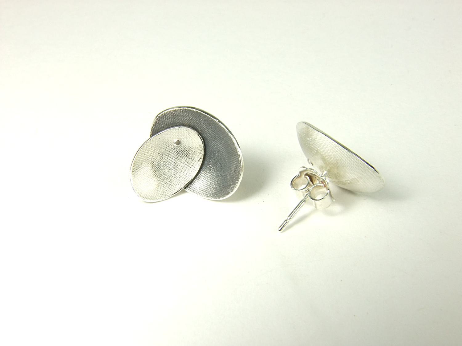Rear view of large Argentium silver ear studs with two domed oval shapes, partially oxidised. (HBM088B)