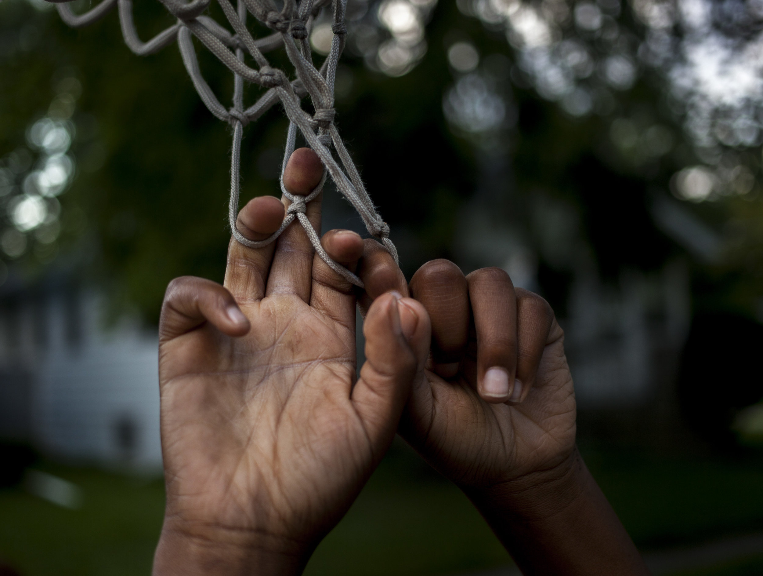 Boop Hardy, 10, hangs from the net outside a friend's house during a pick up game of basketball on Saginaw's Westside. Street basketball in Saginaw, Mich. is a way to form community among the kids of the neighborhood as friendships form and their basketball skills are put to the test.