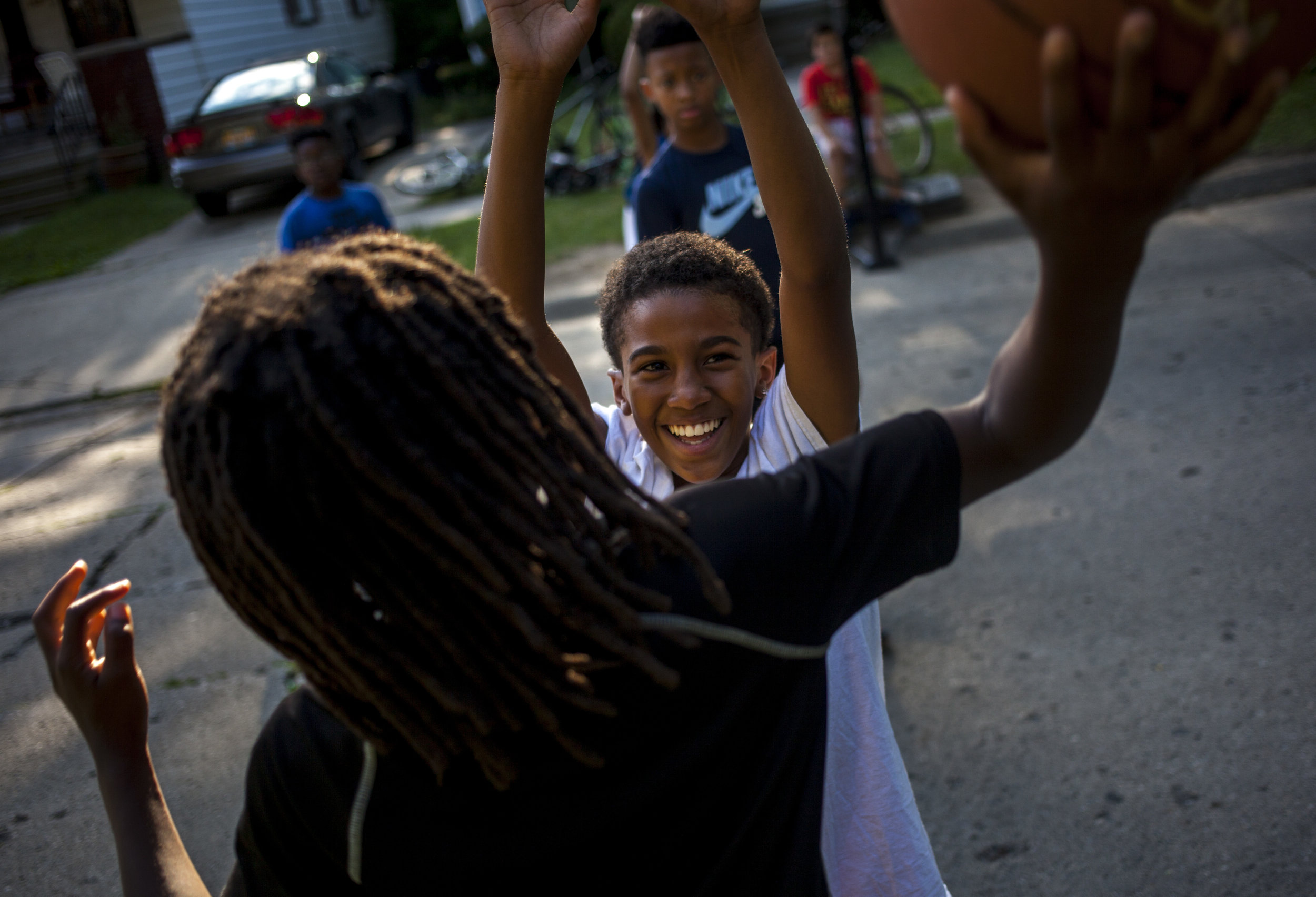 Cayden Gomez, 12, grins as he tries to block his friend Boop Hardy, 10, during a game of basketball outside their friend's house on Saginaw's Westside.
