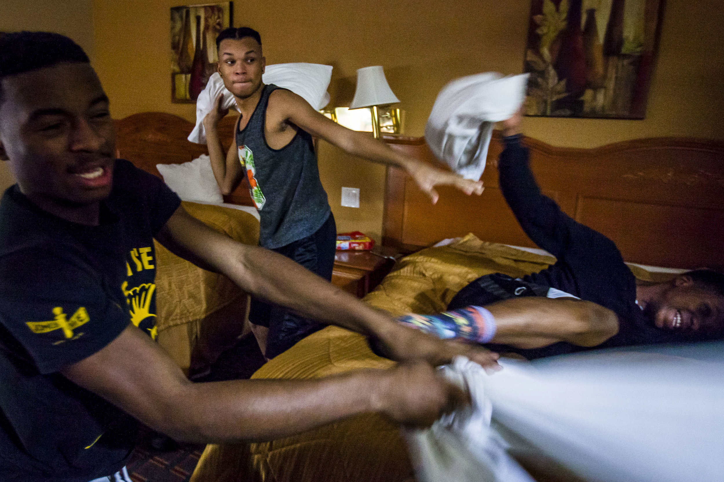 Darquese Doster, left, and Terry Fifer swing their pillows at Jamia Bates in the midst of a pillow fight against the girls at the hotel where the Saginaw High School Marching Band, better known as the Mighty Marchin' Trojans, stayed in Atlanta, Ga.