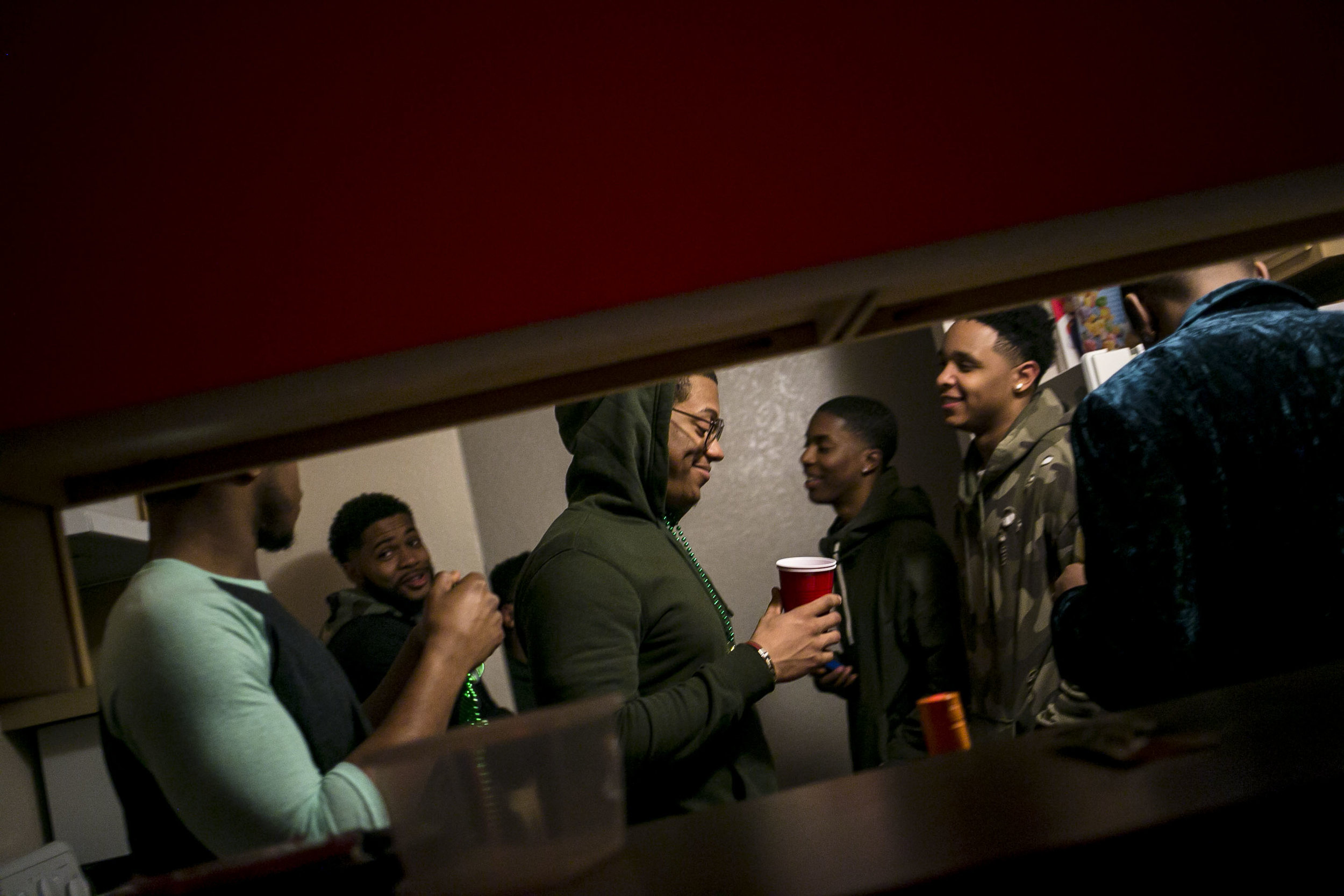 During a party for his 21st birthday Trenton Carson smiles to himself as he is surrounded by his fraternity brothers.