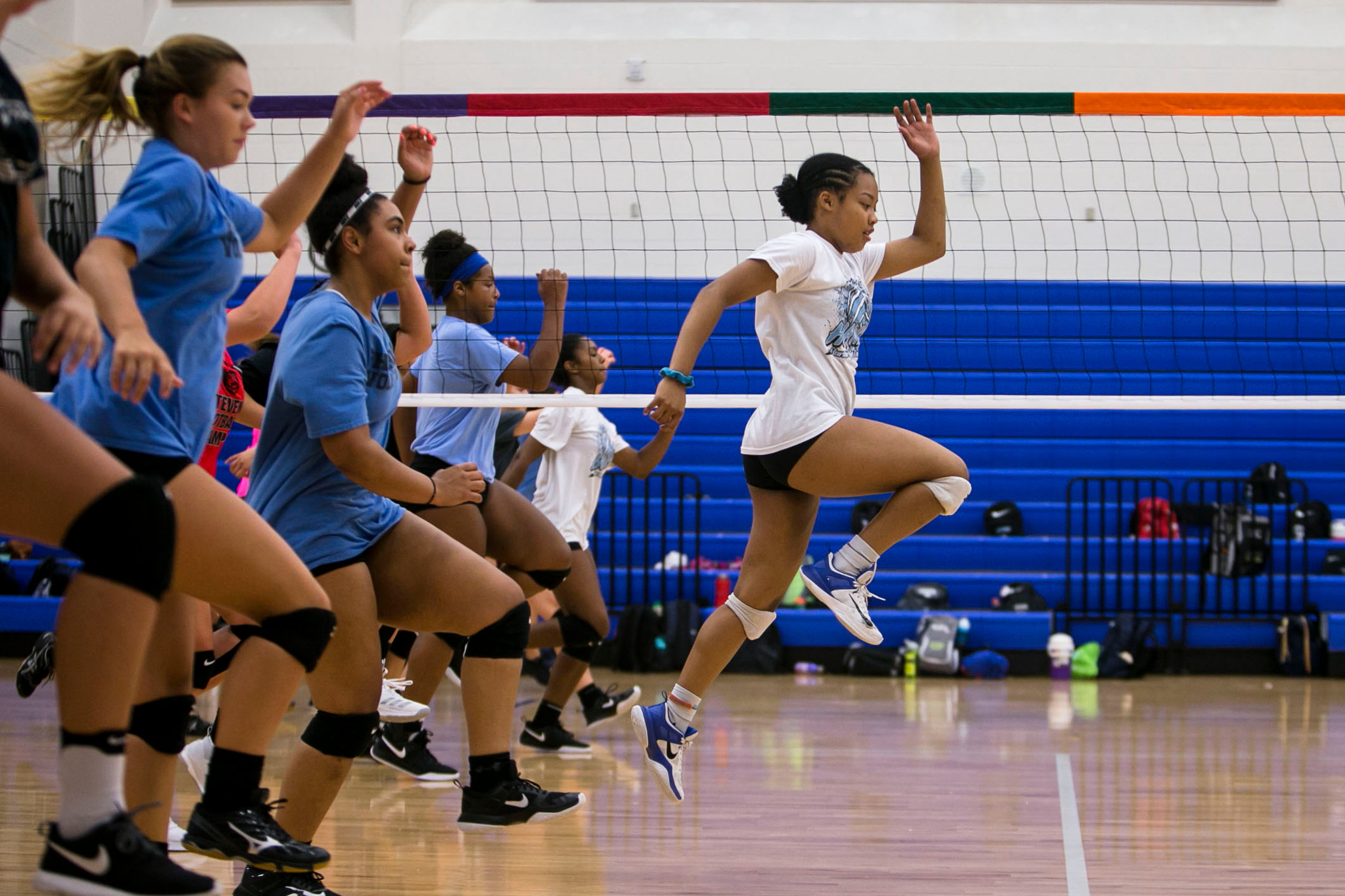 During varsity volleyball tryouts, Jevani Hanspard, 16, takes the lead leads the pack of volleyball hopefuls during a conditioning drill Harlan High School.