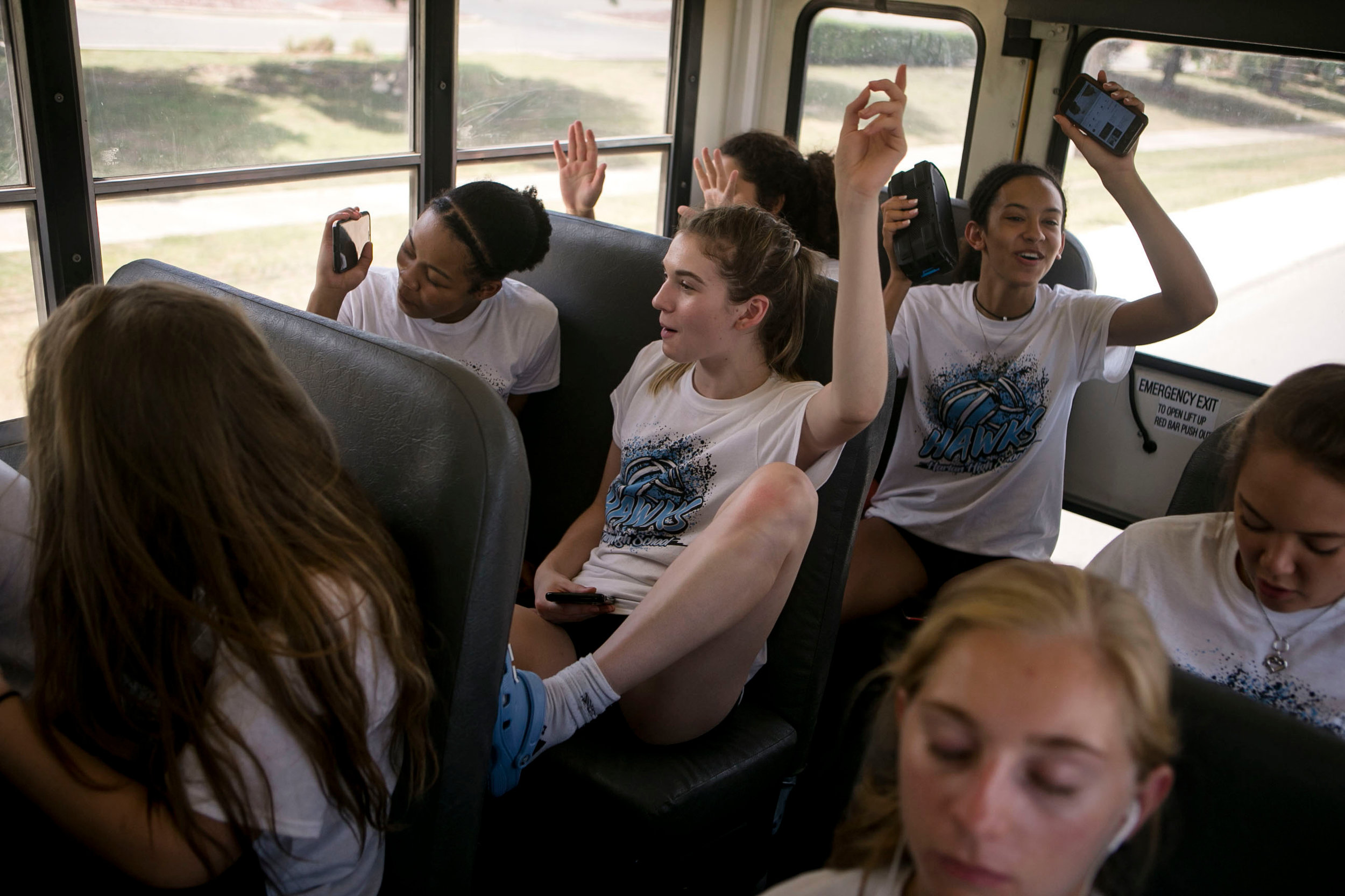 .On the way home from the Harlan High School varsity volleyball scrimmage, the girls sing along to music playing on speakers at the back of the bus.
