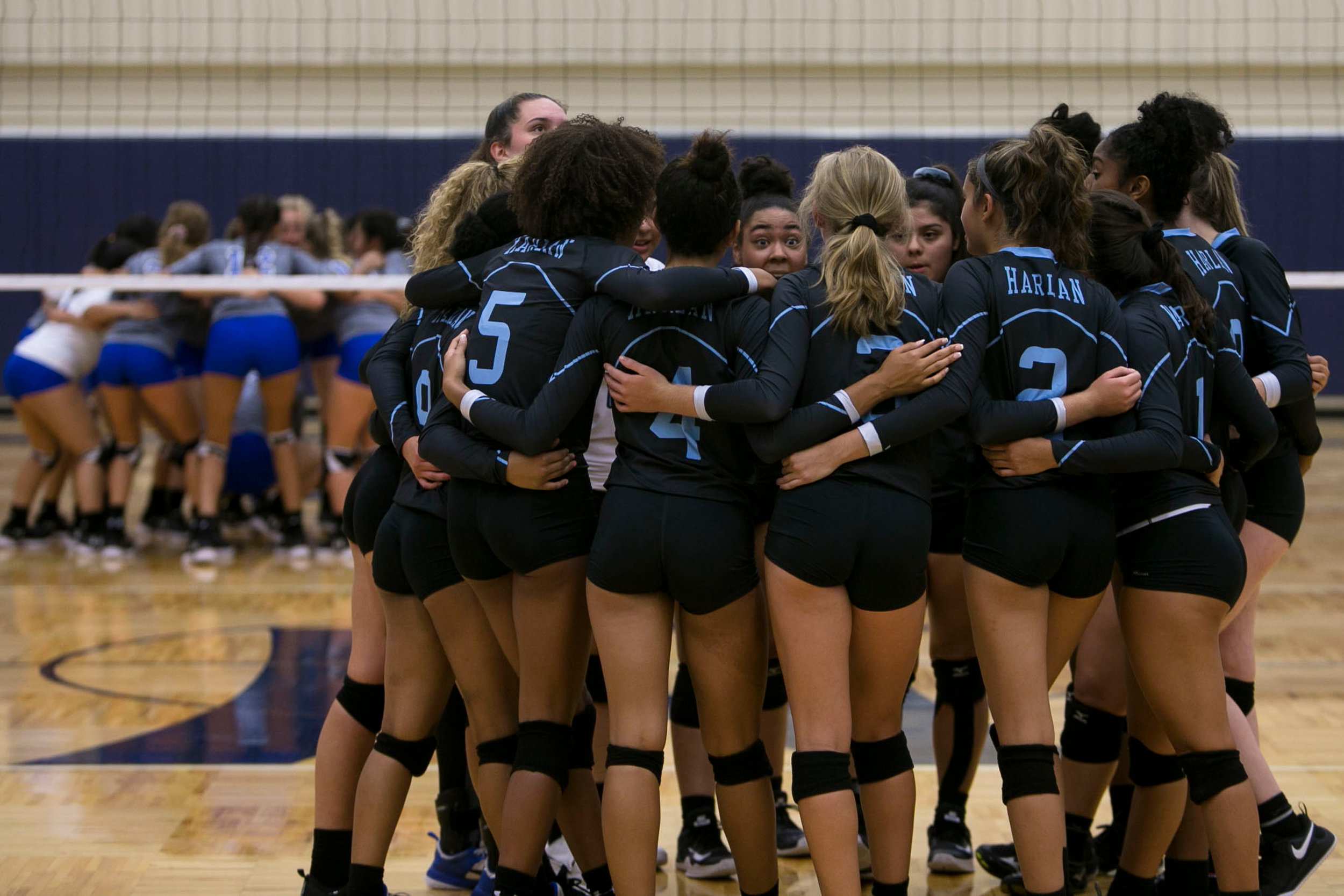 The first Harlan varsity volleyball team huddles up before their first game at Paul Taylor Fieldhouse.