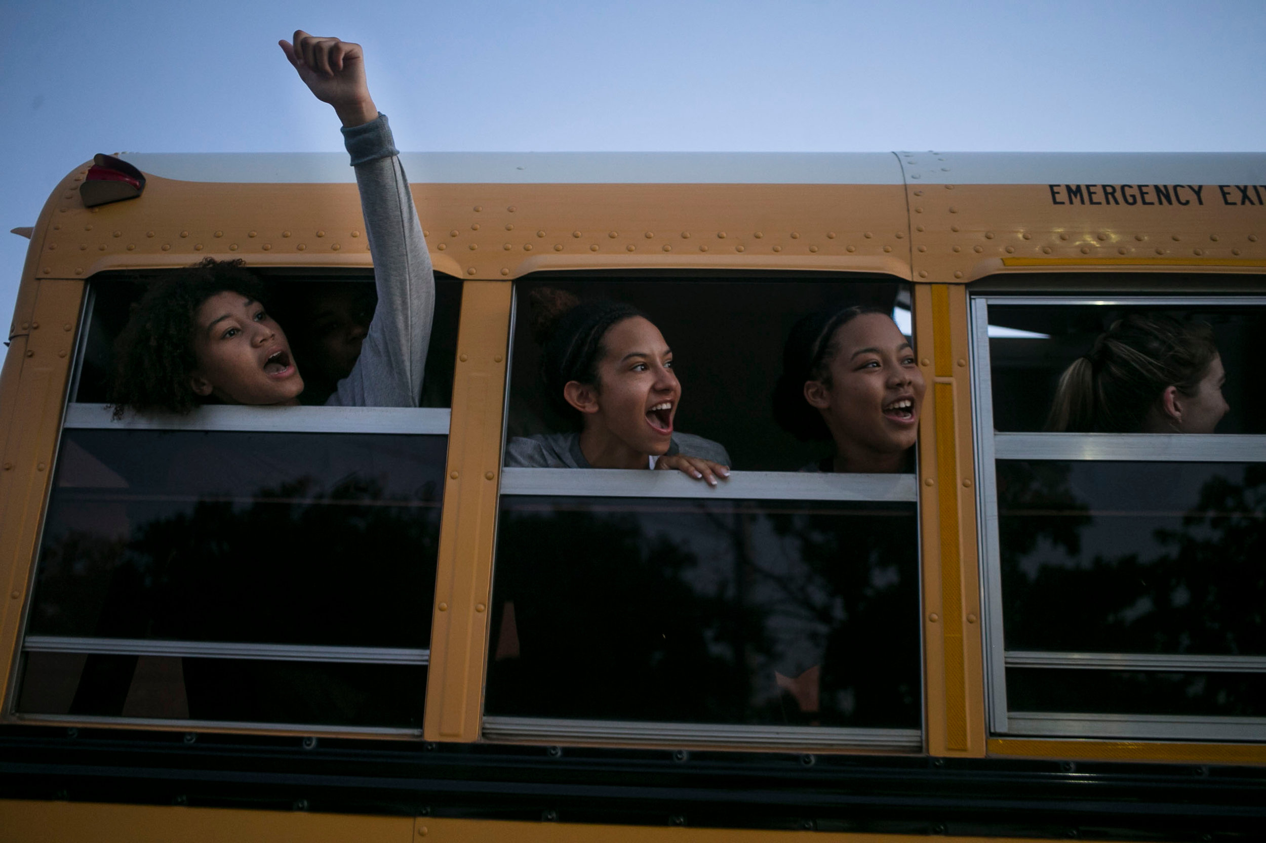 Ayanna Jackson, 16, Ashley Chatham, 16, and Jevani Hanspard, 16, cheer for their coach Monica Gonzales as she walks to the bus after the first Harlan Varsity Volleyball win at Paul Taylor Fieldhouse. The team beat their opposition 3-0 and spirits flew high as they began their seaon together.