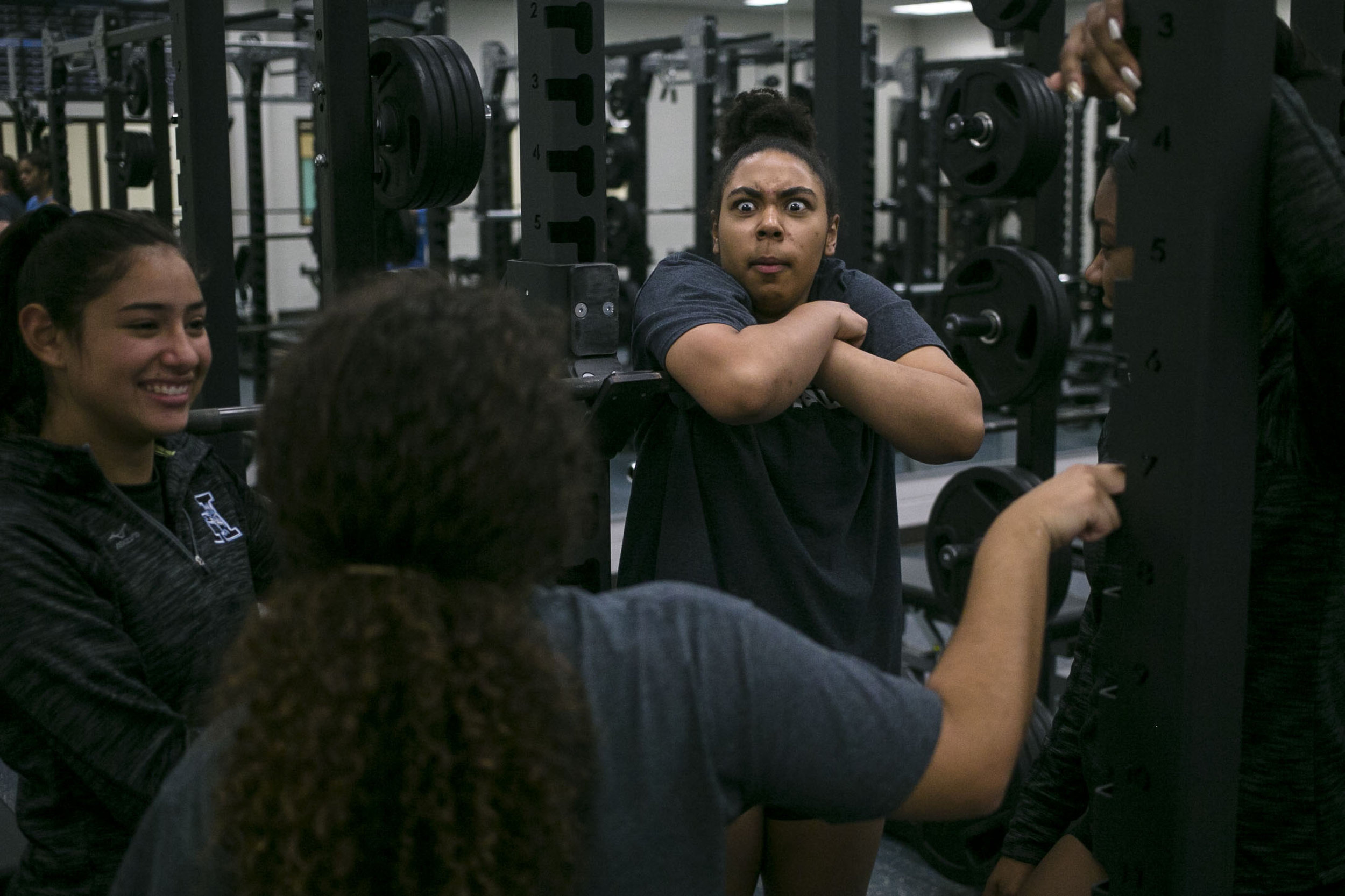 Victoria Thames, 17, reacts to a piece of gossip in between sets during a team session weight training Harlan High School.
