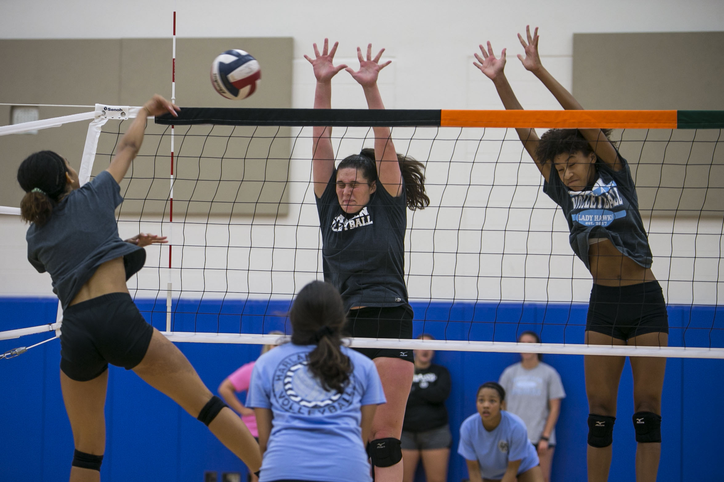 Amaia Martin, 16, and Ayanna Jackson, 16, squeeze their eyes shut as they jump to block Ashley Chatham's, 16, hit during the first day of volleyball tryouts at Harlan High School.