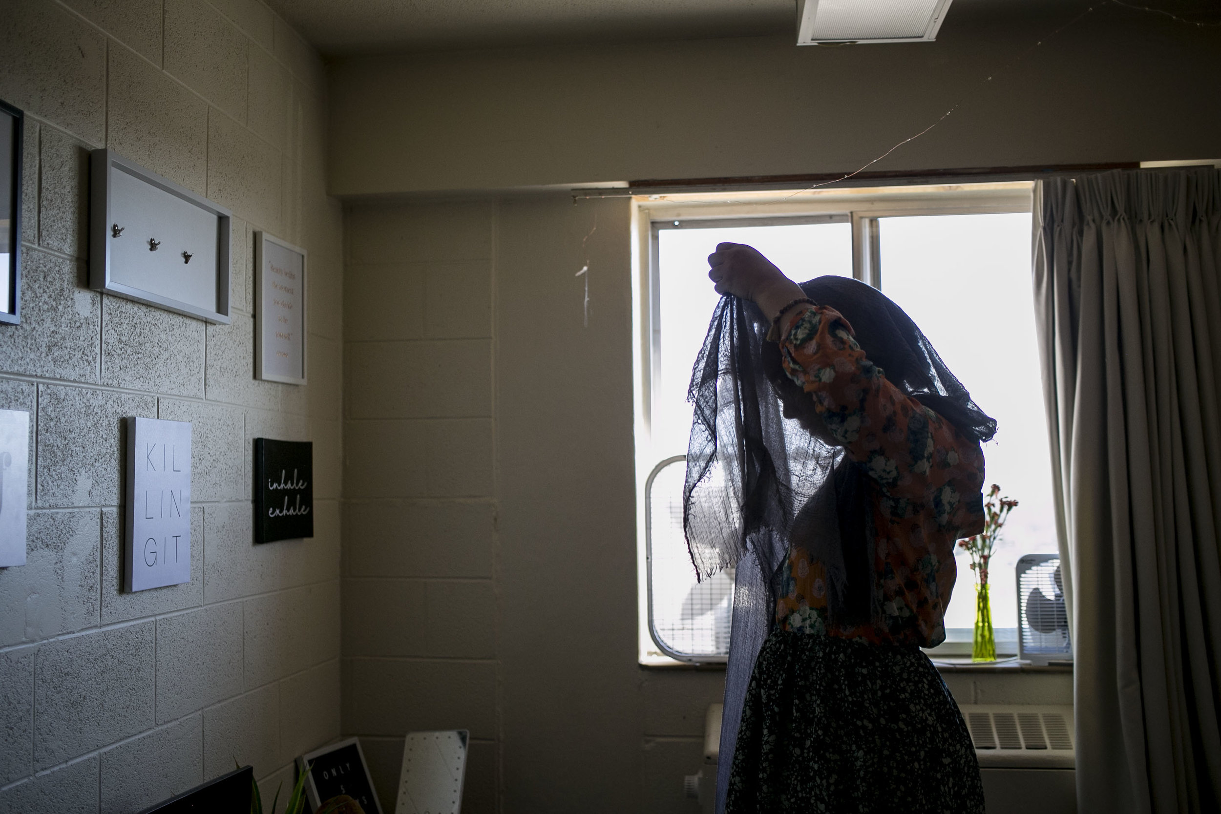 "As she prepares for one of her five daily prayers, Riley drapes her head scarf over her head in her dorm room. Since starting covering her hair, Riley makes a point to not post pictures of her self in a hijab on social media for concern of someone from her hometown seeing that she has converted and it having a negative impact on her parents' lives. While her parents are very supportive and accepting of her decision to convert, when Riley is at home she wears a turban rather than a hijab. ""I try my best to not stand out a lot (while covering)… Which sucks because I'm proud to be Muslim but also I don't want to be killed."""