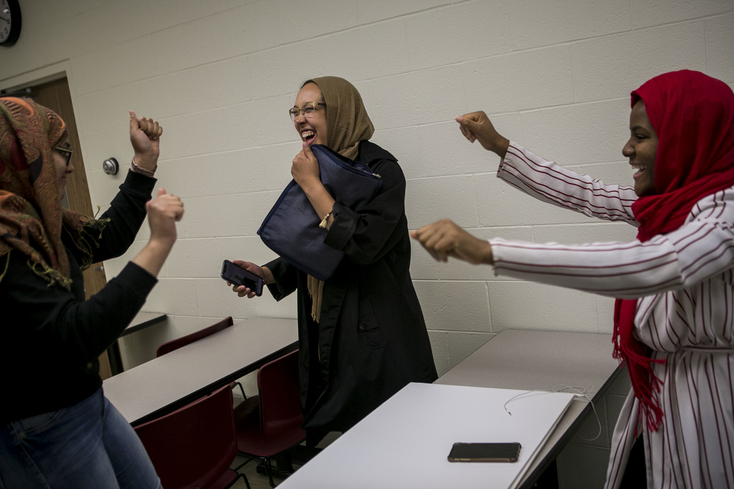 Riley laughs as her friends Manahil Khan, left, and Halima Abdi, dance around her after a meeting of the Muslim Student Association on the campus Central Michigan University in Mt. Pleasant, Mich.