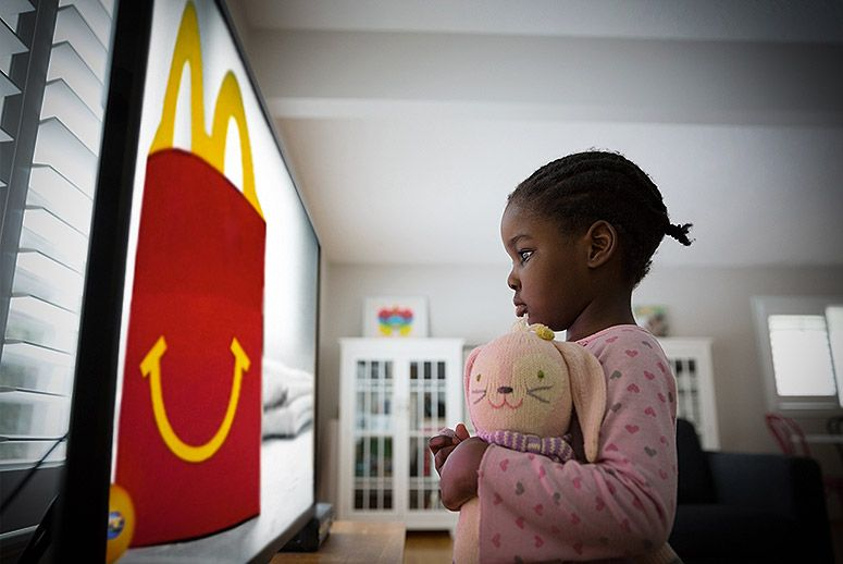 Little girl staring at fast food ad on tv