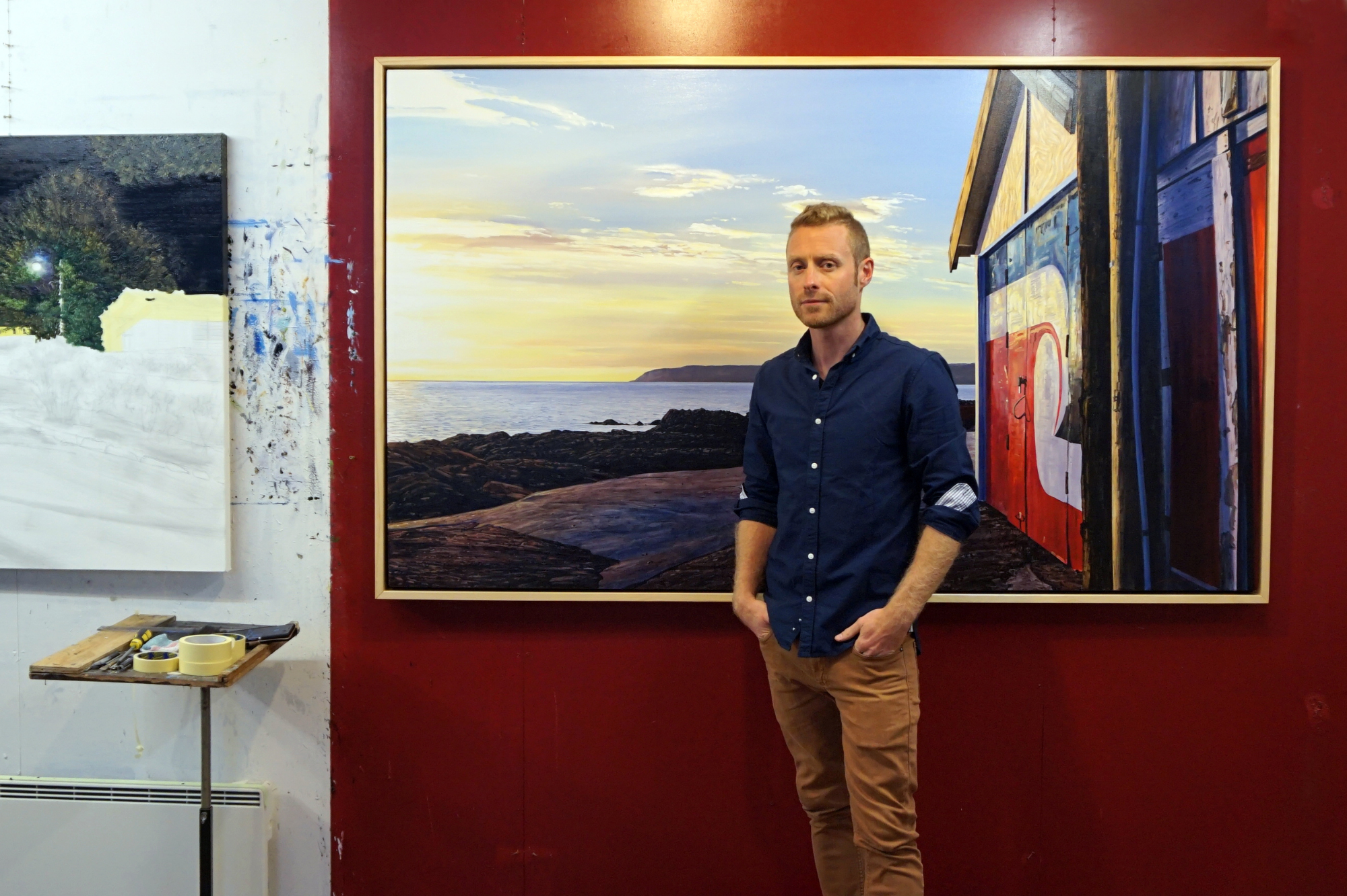 Artist Sam Foley in front of one of his paintings destined for the Pataka exhibition.