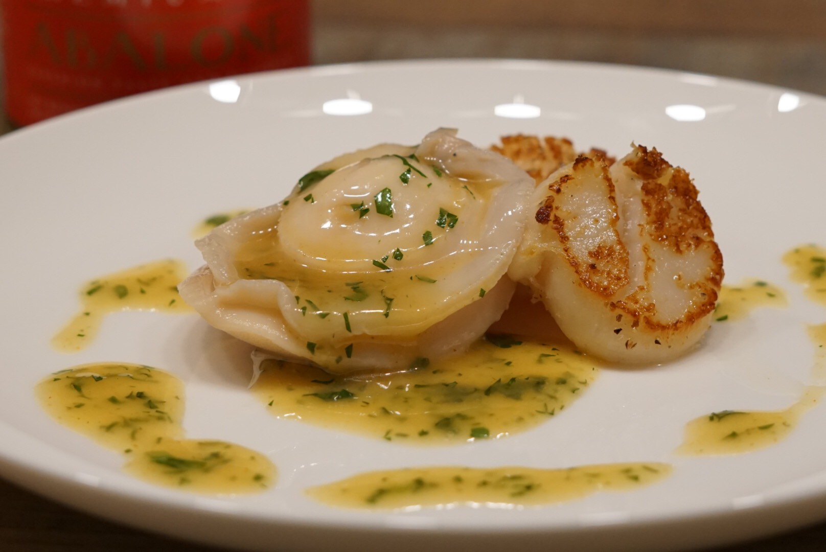ABALONE AND SCALLOPS SERVED IN A SCALLOP AND HERB SAUCE