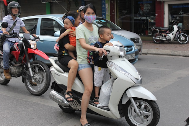 A family rides on a motorbike--a typical scene in Hanoi