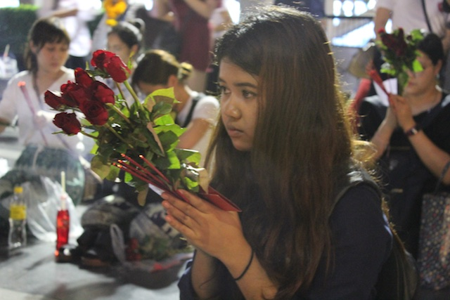 A young Thai lady prays for love at the Trimurtri Shrine near the Isetan store in midtown