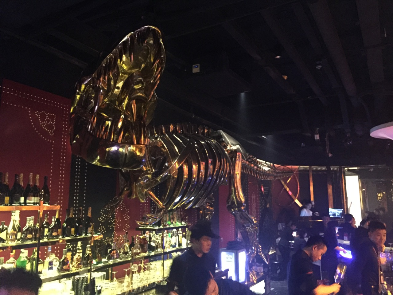 A chrome dinosaur haunts the bar at Mix club in Gongti
