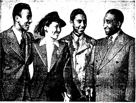 GLAD TO BE IN THE GOOD OLD U. S. A. are Mr. and Mrs. William (Bill) Hegamin and their two sons, Jerome 16, (left), and Robert 17, (right) after two years and seven months of privation and cruelty In a Japanese concentration camp in Shanghai, China. Hegamin, a well-known New York pianist and composer, went to Shanghai 20 years ago where he amassed a small fortune in the music business only to have it ruthlessly confiscated by the Japs. Homeless, the family, some of the last of the repatriated Americans, left Shanghai on the hospital ship USS Refuge to Okinawa, then by the CSS Santuary to San Francisco, arriving in New York City last week, where they plan to live and educate their sons. According to their blood curdling story of death, destruction and atrocities in Shanghai during the Japanese occupation they are indeed fortunate to be alive and together.