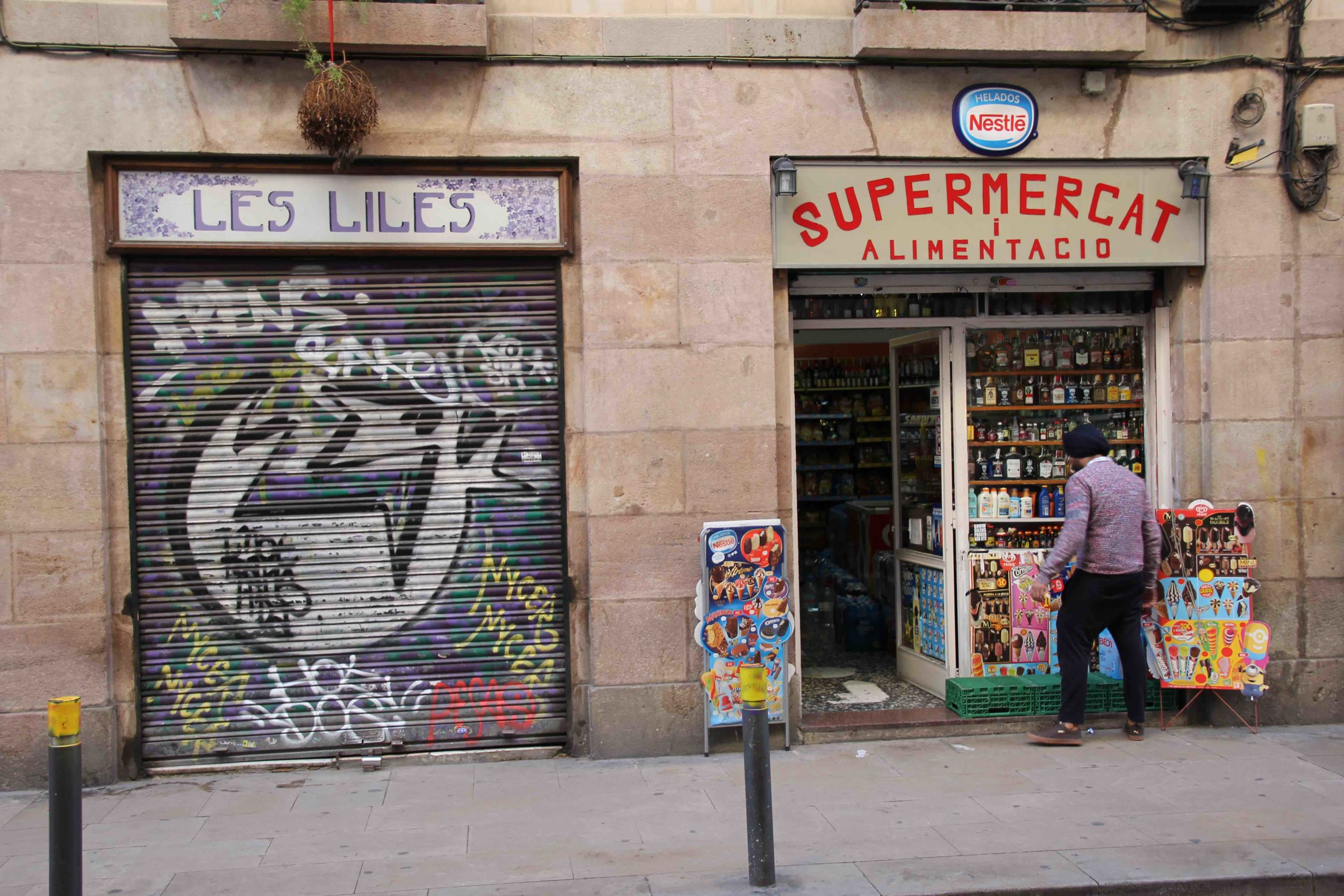 A supermercat in Barcelona run by a Sikh, and next to it a work of graffiti on the shutter of the shop which is very typical of Barcelona street art.