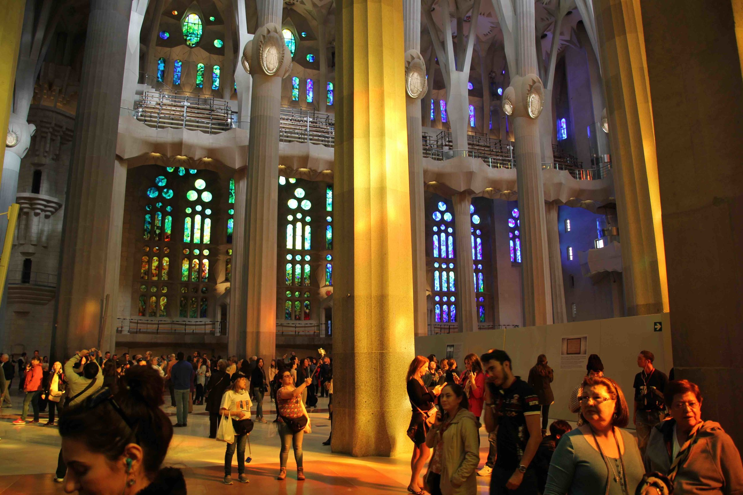 The interior of La Sagrada Familia. Note the blue and green light emanating from the far windows on the nativity side, and the reflections of red, orange and yellow light on the pillars from the windows on the passion side.