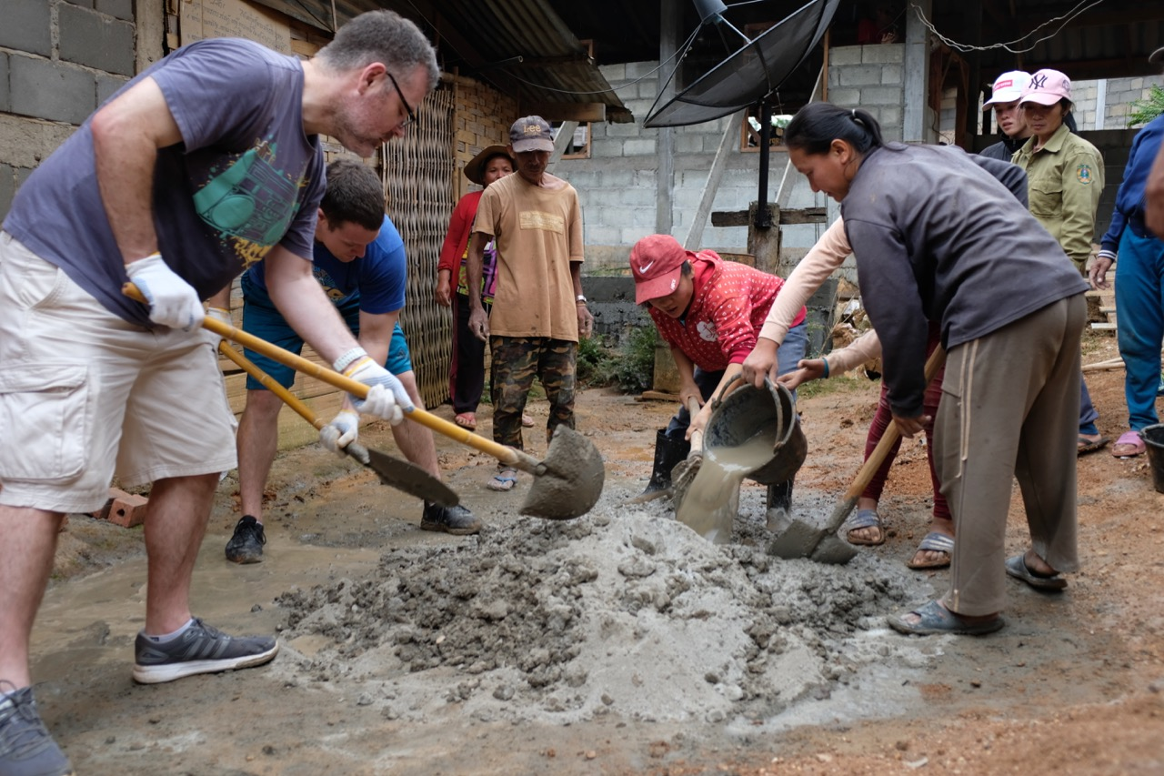 Two of our teachers, Tom and Nate, use their ample muscles to help some of the villagers to mix cement for the platform. This was tough work!