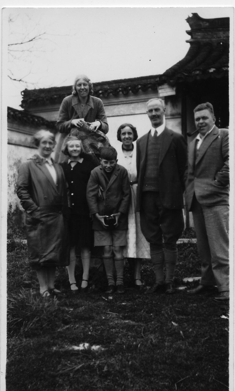 S. C. Young (second from right), Mrs. Young (to his left) and Albert Norman Young with family friends posing in front of a Chinese style building probably in the 1930s