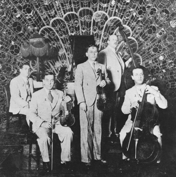 An ensemble of musicians posing in front of the peacock fan orchestral shell at the Astor House (1930s)