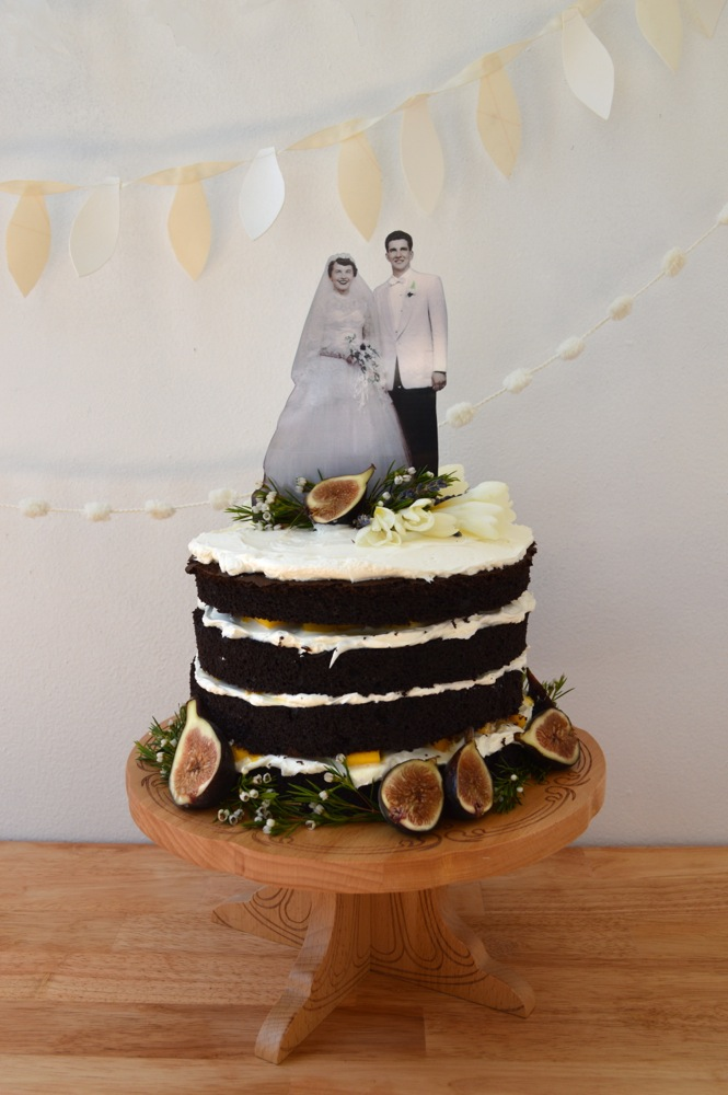 A homemade cake with fluffy frosting and fresh mango between the layers. Topped with a family photograph, fresh flowers, and figs.