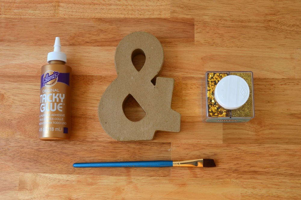 For the topper you will need a cardboard ampersand, glue, a brush, and a variety of non-toxic gold glitter.