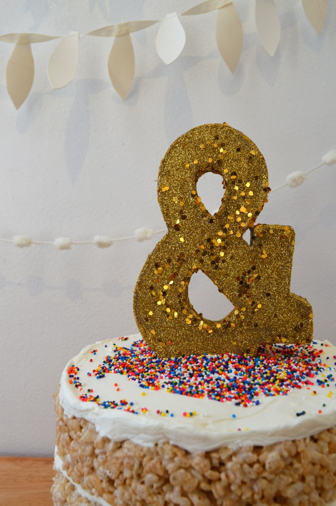 Cover the top of the cake with another layer of frosting, rainbow sprinkles, and then place the finished dry ampersand on top.