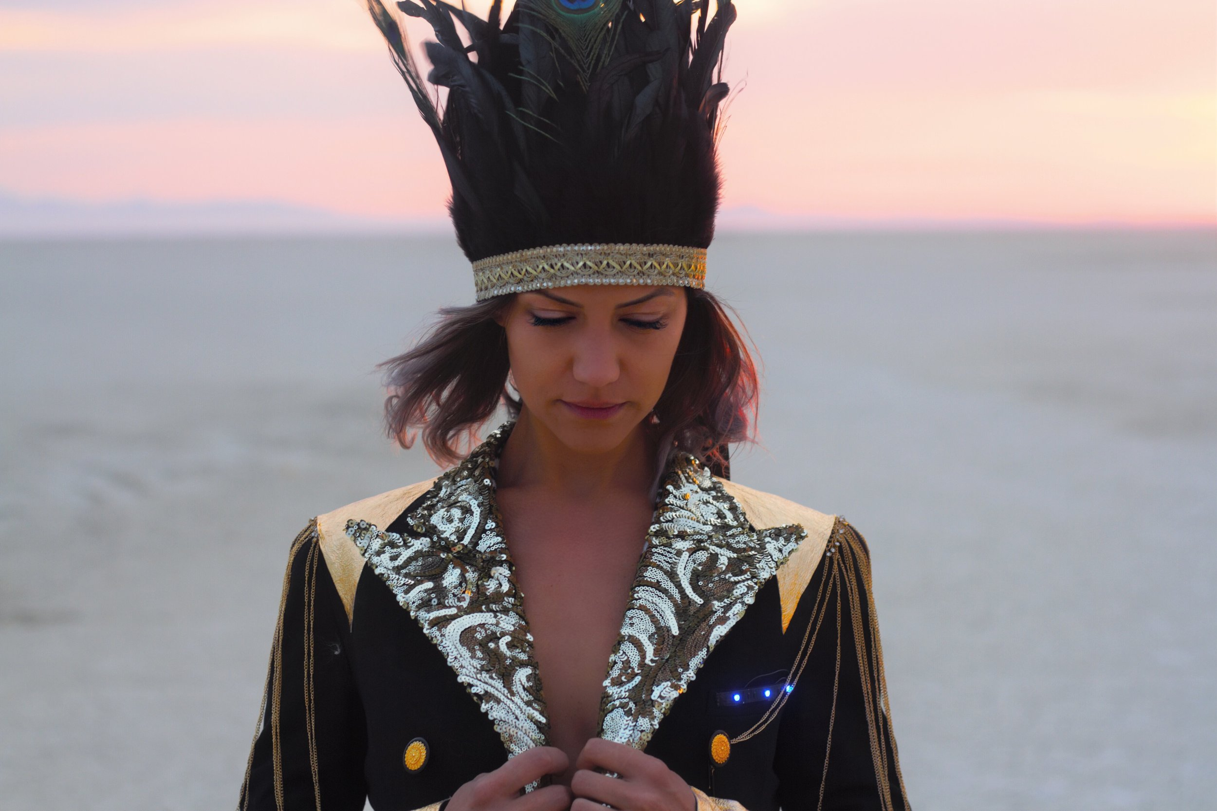 girl wearing a black feather headress and a black and gold sequin jacket