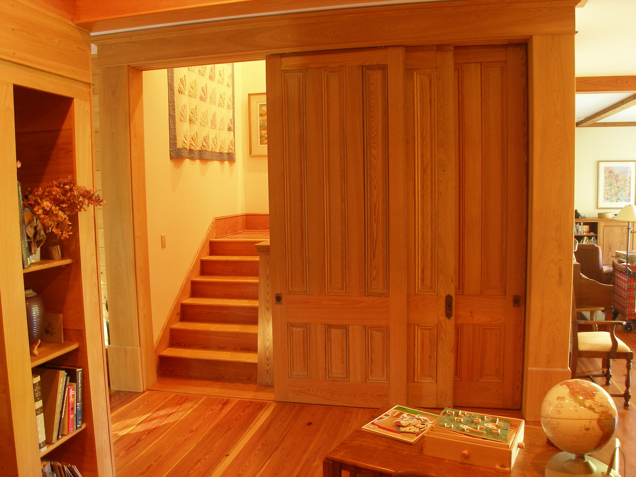 Tall cypress doors open showing stairs to guest bedroom and tower.