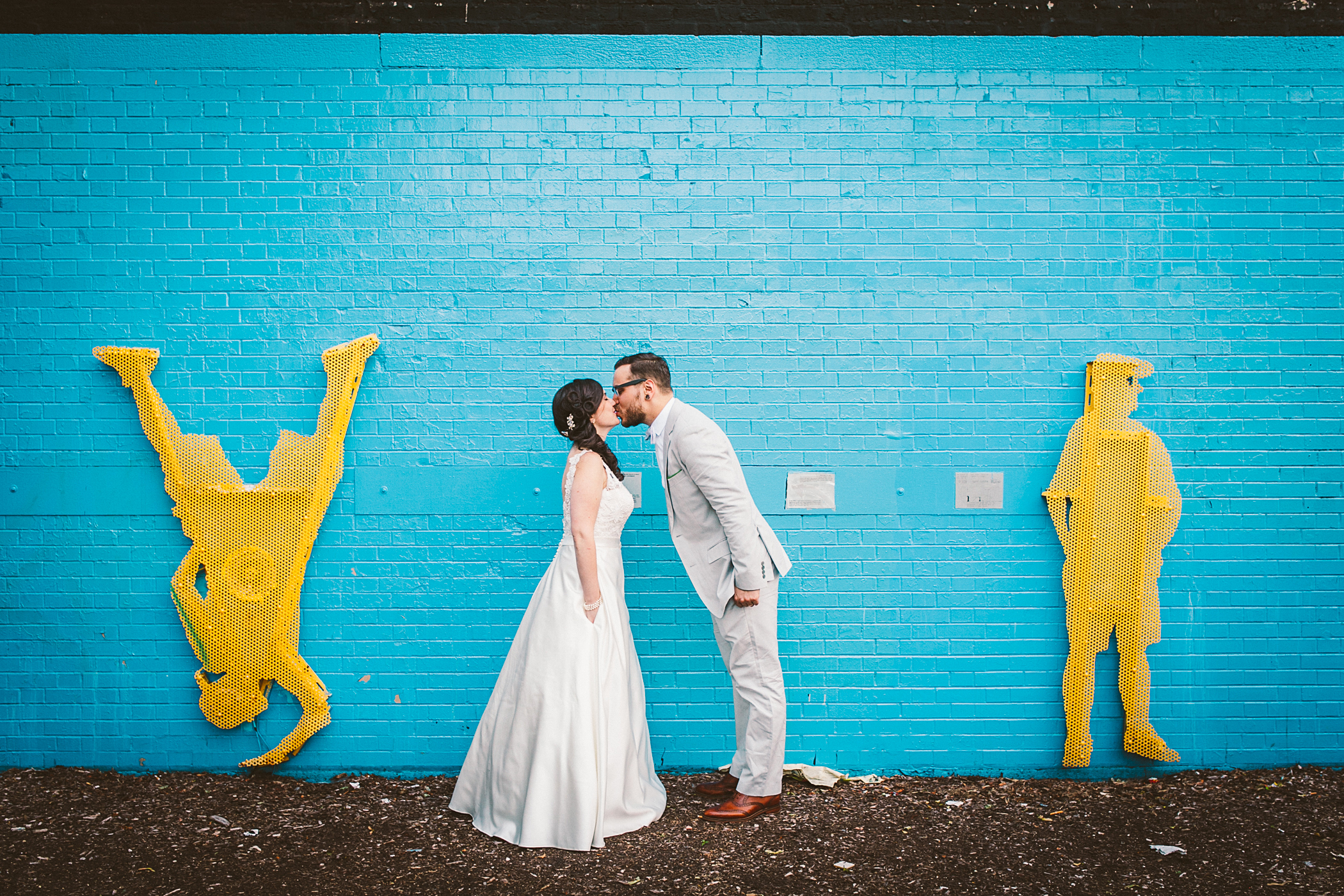 Oriana Koren Weddings kiss in front of wall with mounted sculptures