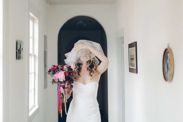 Betty Clicker Wedding Photography bride touching veil and holding bouquet