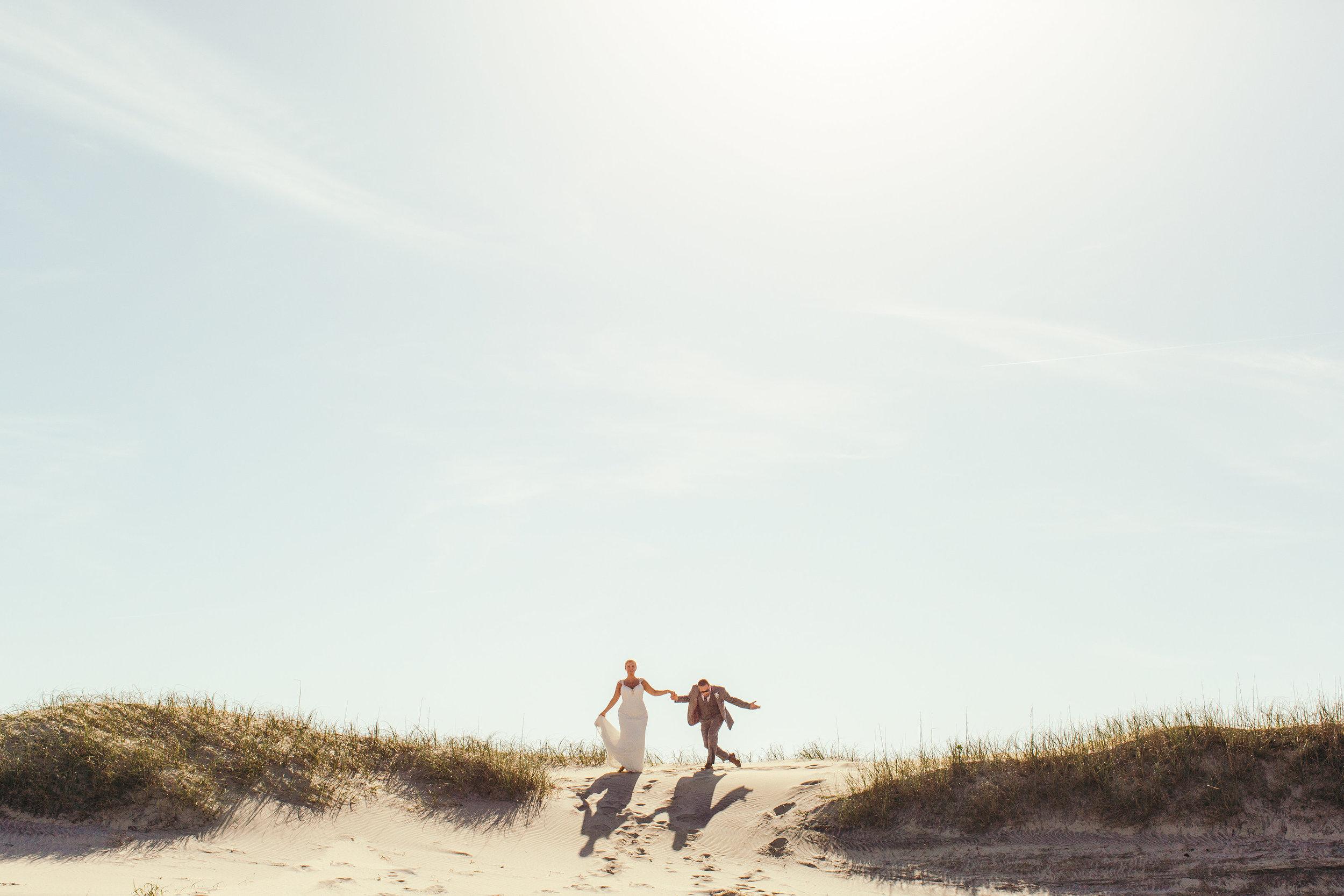 Betty Clicker Wedding Photography couple running on sand dunes