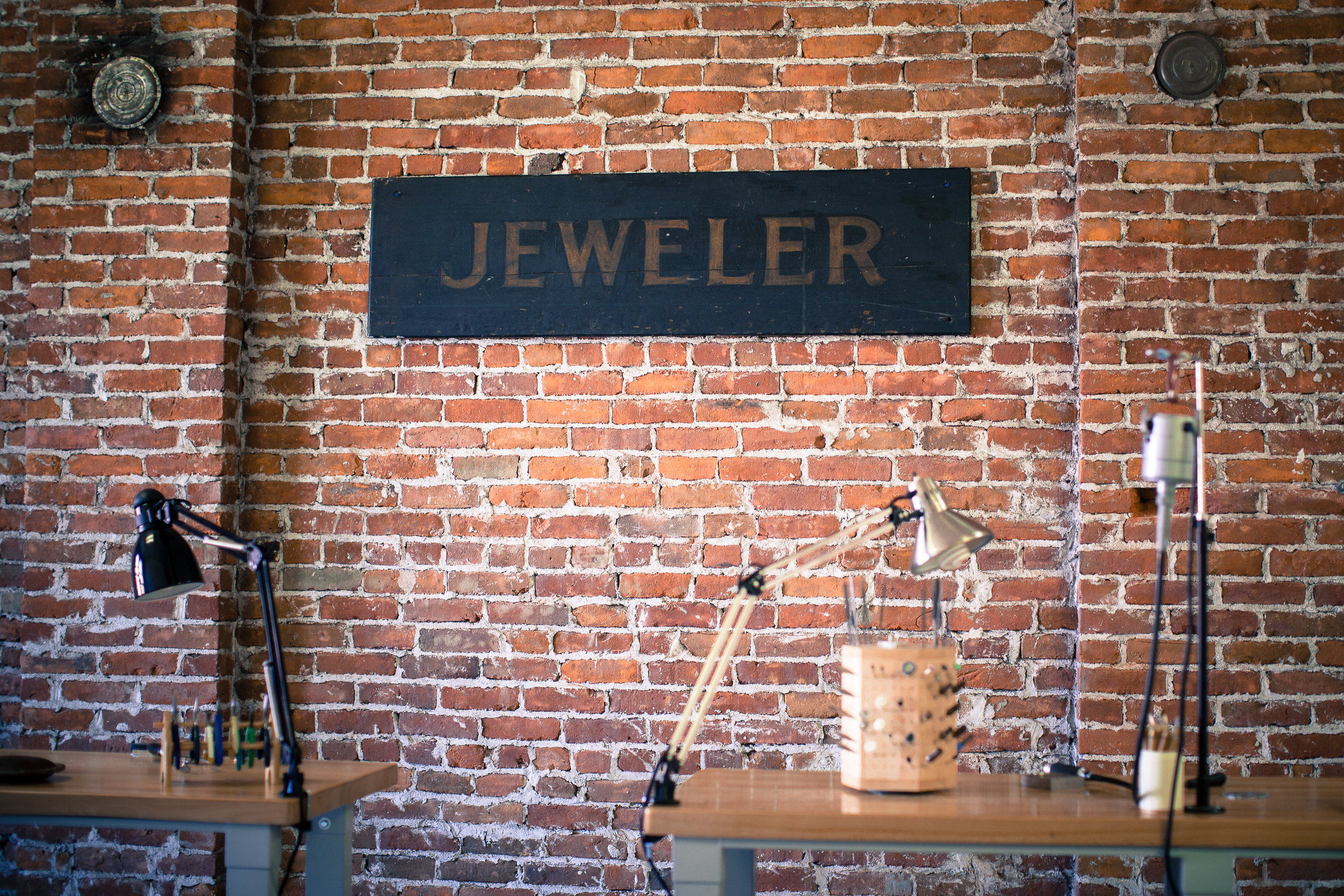 """with these rings work station with sign reading """"jeweler"""""""