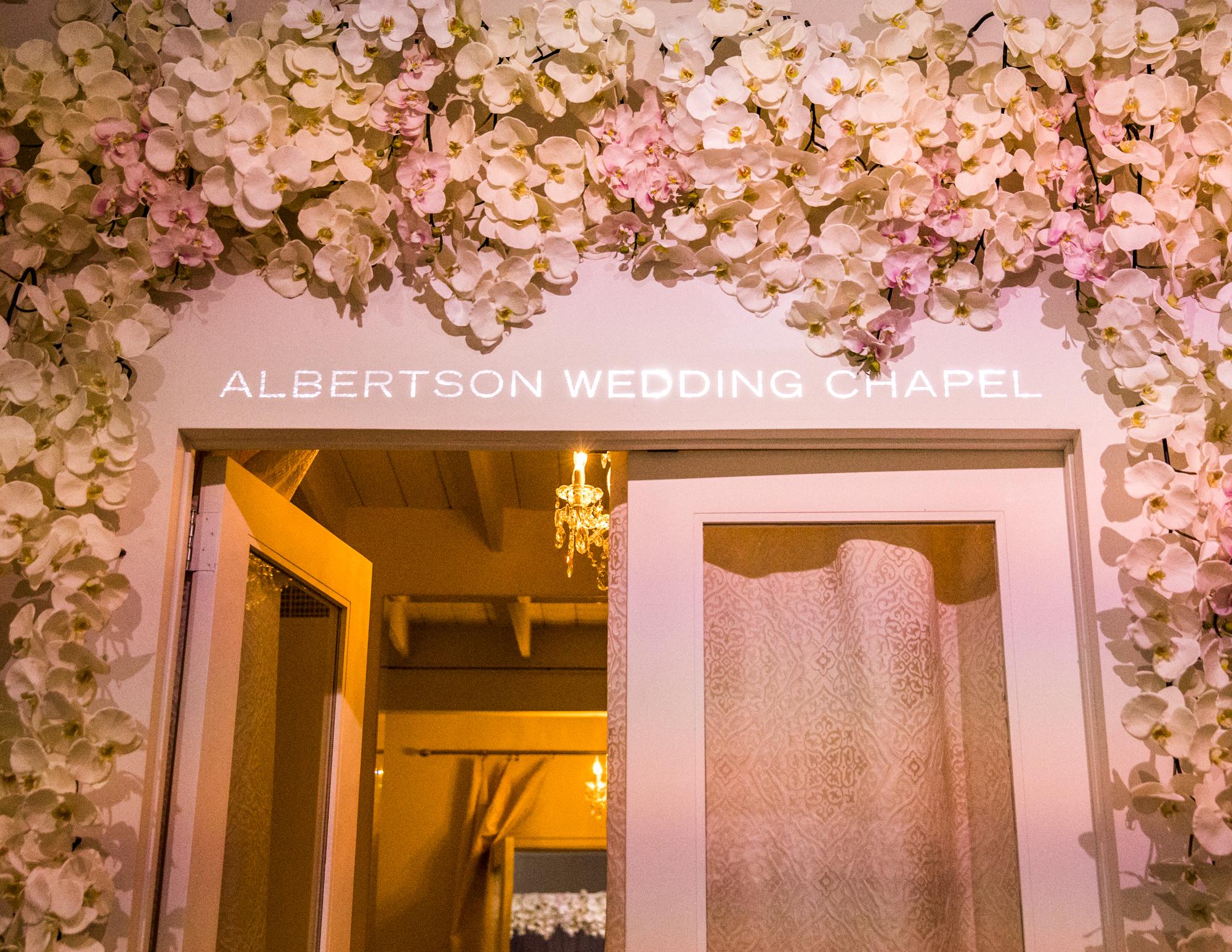 """Colleen Stavrakos Wedding Photography door surrounded by flowers, writing above door reading """"Albertson wedding chapel"""""""