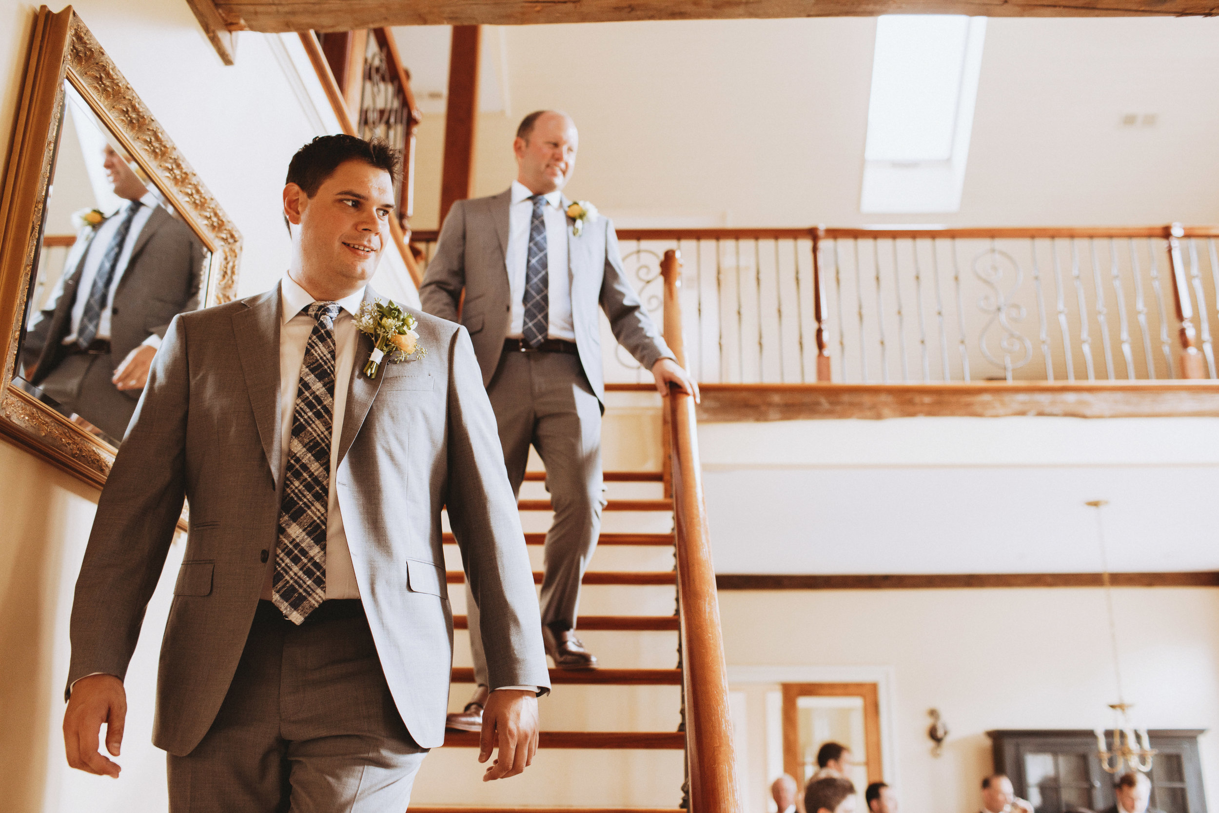 two grooms at their wedding heading downstairs to greet guests