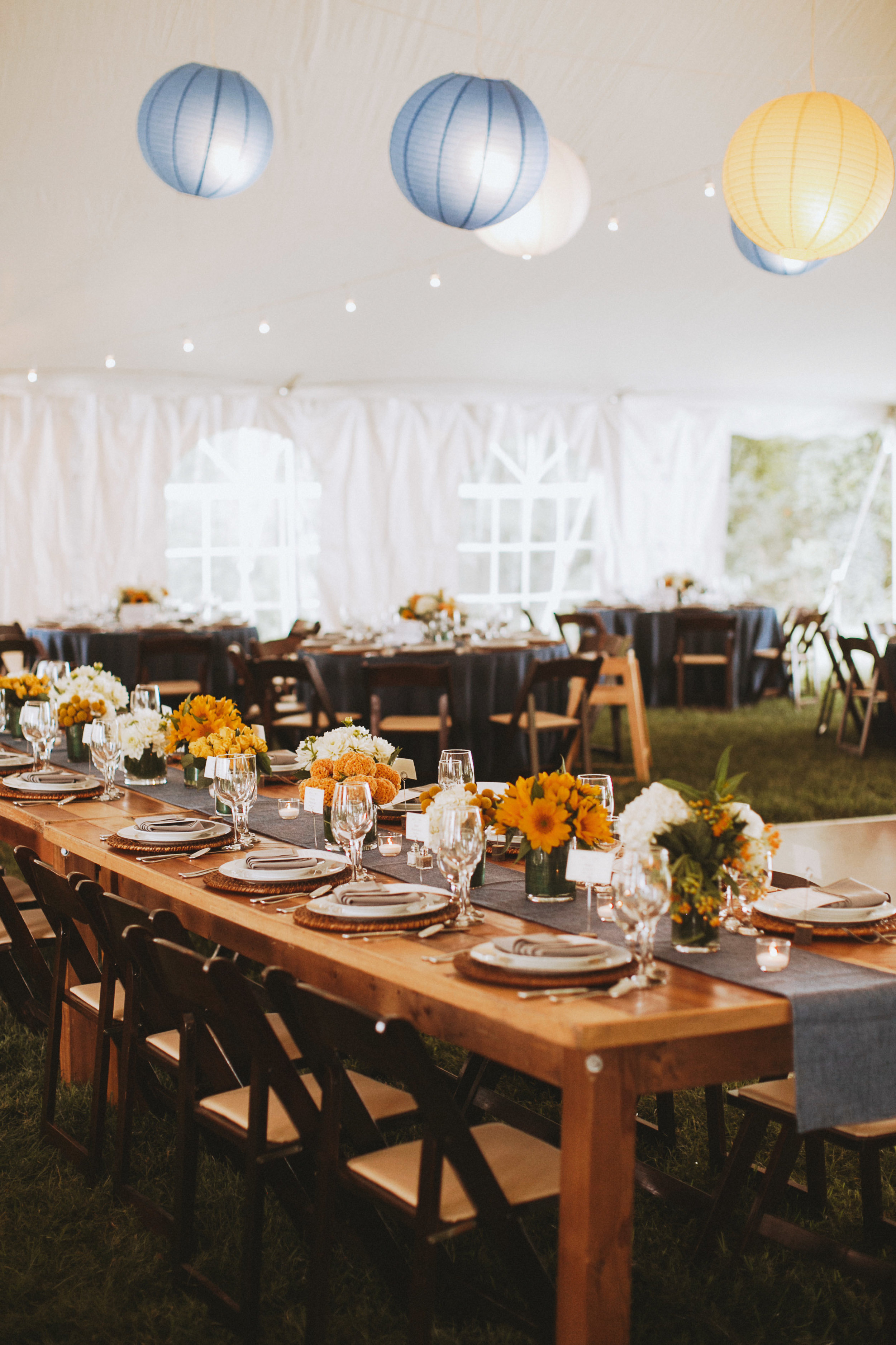 sunflowers and paper lanterns at a tented wedding