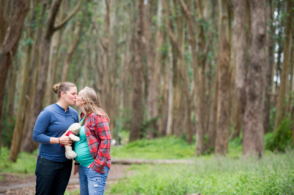 Same-sex maternity photos in San Francisco's woods, holding a teddy bear.