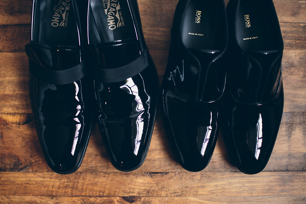 Two pairs of black patent leather men's dress shoes.