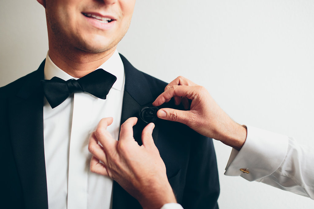 One groom helps his future husband with a boutonniere.