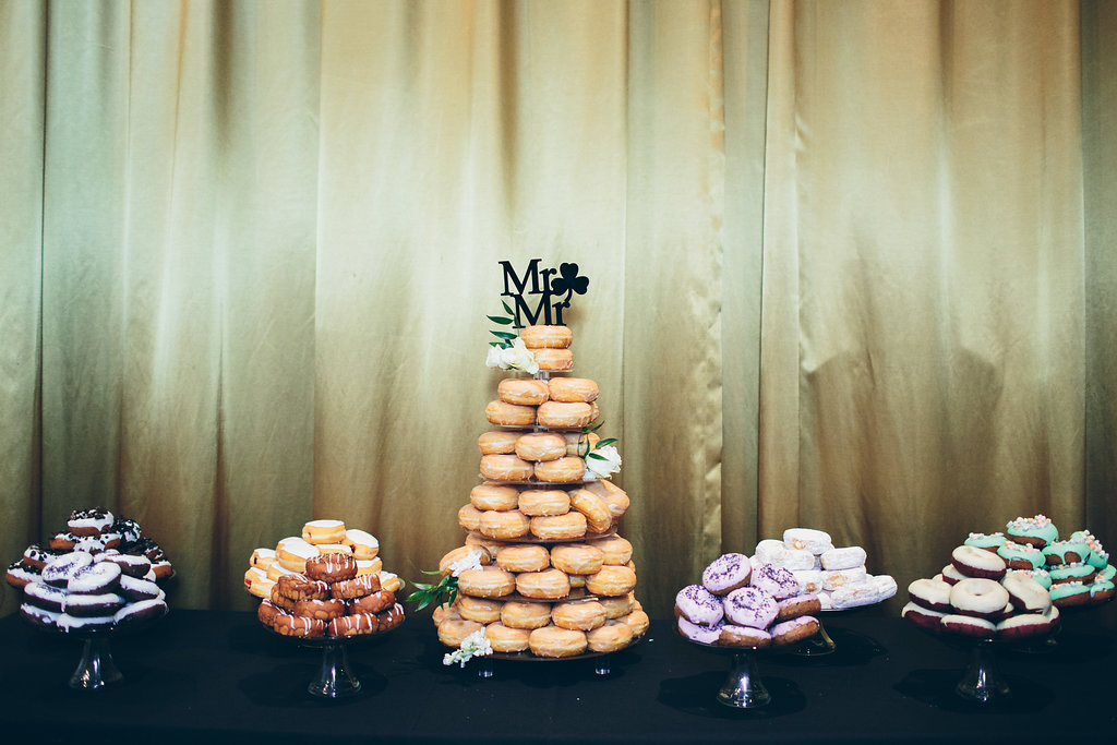 Mr. and Mr. cake topper on a tower of doughnuts.