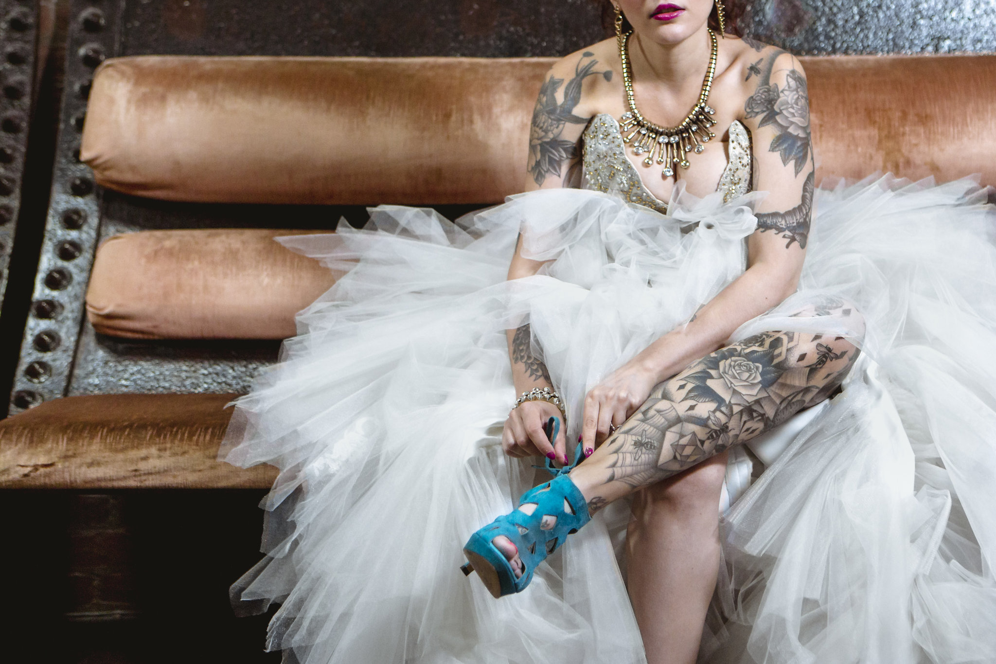 Tattooed bride putting on her shoes.